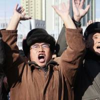 North Koreans cheer outside Pyongyang Station as they watch a news broadcast announcing the test-firing of the newly developed Hwasong-15 intercontinental ballistic missile on Wednesday. | AP