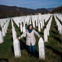 A woman mourns over a relative's grave at the memorial center of Potocari near Srebrenica on Wednesday. United Nations judges on Wednesday sentenced former Bosnian Serbian commander Ratko Mladic to life imprisonment after finding him guilty of genocide and war crimes in the brutal Balkans conflicts over two decades ago.   AFP-JIJI