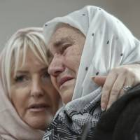 Bosnian women are overwhelmed by emotion watching the final moments of former Bosnian Serb military chief Gen. Ratko Mladic's trial at the memorial center in Potocari, near Srebrenica, Bosnia, Wednesday. A U.N. court has convicted former Bosnian Serb military chief Gen. Ratko Mladic of genocide and crimes against humanity and sentenced him to life in prison for atrocities perpetrated during Bosnia's 1992-1995 war.   AP