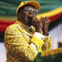 Zimbabwean President Robert Mugabe clenches his fists as he delivers a speech at his party's 13th annual conference, in Gweru, about 250 km southwest of Harare, in December 2012. | AP
