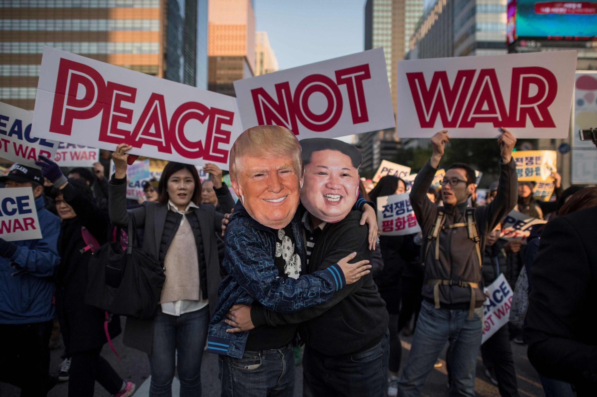 Demostrators wearing masks of North Korean leader Kim Jong Un and U.S. President Donald Trump embrace during a peace rally in Seoul on Sunday. | AFP-JIJI