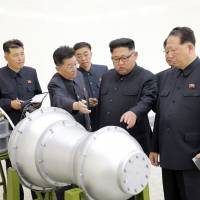 North Korean leader Kim Jong Un visits a nuclear weapons site in this undated photo released Sept 3. The country's state-run media said Kim had inspected the loading of a hydrogen bomb onto a new intercontinental ballistic missile, a claim that could not be independently verified. An apparent diagram of how the supposed bomb would fit onto the tip of the long-range missile is displayed in the background. | AP