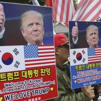 South Koreans hold placards with pictures of U.S. President Donald Trump during a rally welcoming him ahead of his visit to the country in downtown Seoul on Friday. | AP