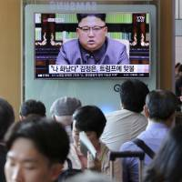 People at Seoul Station watch a broadcast of North Korean leader Kim Jong Un responding to U.S. President Donald Trump's speech to the United Nations in September. | AP