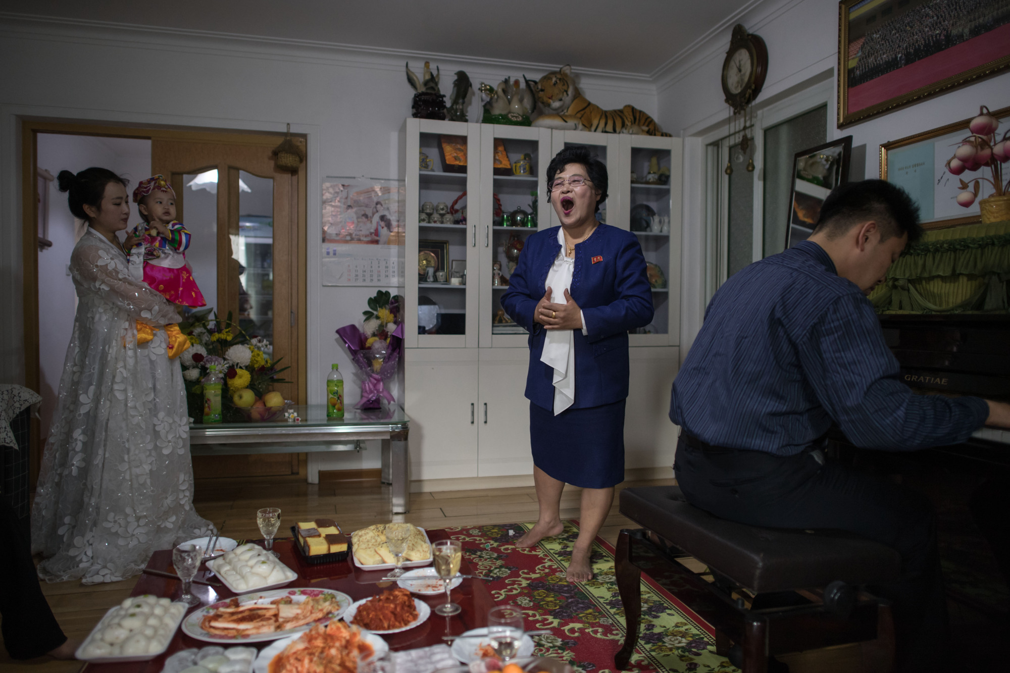 Eyeglass shop manager Song Song-Hui sings for her family members in her apartment in Pyongyang on Nov. 17. | AFP-JIJI