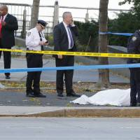Authorities investigate the scene around a body covered under a white sheet next to a mangled bike along a bike path Tuesday in New York.   AP
