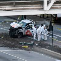 Investigators inspect a truck following a shooting incident in New York on Tuesday. Several people were killed and numerous others injured in New York on Tuesday when a man plowed a vehicle into a bike and pedestrian path in Lower Manhattan, and struck another vehicle on Halloween, police said. A suspect exited the vehicle holding up fake guns, before being shot by police and taken into custody, officers said. The motive was not immediately apparent.   AFP-JIJI