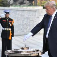 U.S. President Donald Trump burns incense at the National Cemetery in Seoul on Wednesday. Trump offered North Korean leader Kim Jong Un what he called 'a path towards a much better future' as tensions soar over Pyongyang's nuclear ambitions. | AFP-JIJI