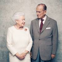 A handout photo shows Britain's Queen Elizabeth and Prince Philip in the White Drawing Room at Windsor Castle in early November, pictured against a platinum-textured backdrop, in celebration of their platinum wedding anniversary on Monday. | MATT HOLYOAK / CAMERAPRESS / PA WIRE / HANDOUT / VIA REUTERS