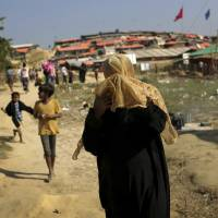A Rohingya Muslim woman covers her face from the afternoon dust and heat as she walks through the Jamtoli refugee camp on Monday in Bangladesh.   AP
