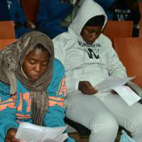 Cameroonian migrants look at registration forms upon their arrival Wednesday after spending several months in Libya, at the Yaounde International Airport in Cameroon. | AFP-JIJI