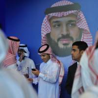 Saudi men chat in front of a poster showing Crown Prince Mohammed bin Salman during a regional forum in Riyadh on Wednesday.   AFP-JIJI