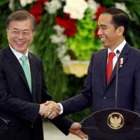South Korean President Moon Jae-in (left) and Indonesian President Joko Widodo shake hands at the end of their joint statement to the media at the presidential palace in Bogor, Indonesia, Thursday. | REUTERS