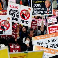 Protesters rallying against Donald Trump wait for the U.S. president's motorcade to pass by in central Seoul Tuesday. | REUTERS