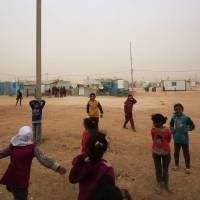 Syrian refugee children play during a sand storm at the Zaatari refugee camp on Monday. Some 80,000 Syrian refugees living in the Zaatari camp will have access to 14 hours of electricity per day instead of eight hours, thanks to the opening of the new solar power station. | AFP-JIJI