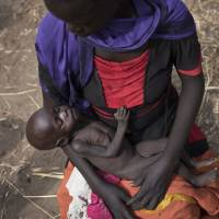 Adel Bol, 20, cradles her 10-month-old daughter Akir Mayen at a food distribution site in Malualkuel, South Sudan, on April 5. In war-torn South Sudan, 1.25 million people are facing starvation, double the number from the same time last year, according to a report by the United Nations and the government released Monday. | AP