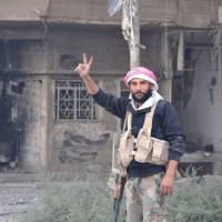 A Syrian pro-government forces member flashes the sign for victory as he patrols in the eastern city of Deir Ezzor on Saturday. Syrian and allied forces converged on holdout Islamic State group fighters in the Syrian border town of Albu Kamal, the jihadis' very last urban bastion following a string of losses. | AFP-JIJI