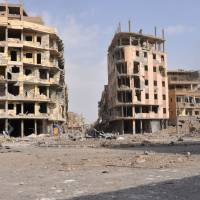 A general view shows damaged buildings in the eastern Syrian city of Deir Ezzor, Syria, on Saturday. Syrian and allied forces converged on holdout Islamic State group fighters in the Syrian border town of Albu Kamal, the jihadis' very last urban bastion following a string of losses. | AFP-JIJI