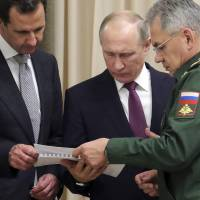 Russian President Vladimir Putin (center), Syrian leader Bashar Assad (left) and Russian Defense Minister Sergei Shoigu examine a document during their meeting in the Bocharov Ruchei residence in the Black Sea resort of Sochi, Russia, on Monday. | AP
