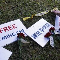 Roses and protest signs are placed on the lawn during a media event on Tuesday in Taipei, Taiwan, to support Taiwanese activist Lee Ming-che, who is being detained in China. | AP