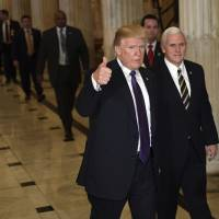 President Donald Trump gives a thumbs up as he walks with Vice President Mike Pence as he departs Capitol Hill in Washington Thursday. Trump urged House Republicans Thursday to approve a near $1.5 trillion tax overhaul as the party prepared to drive the measure through the House. Across the Capitol, Democrats pointed to new numbers showing the Senate version of the plan would boost taxes on lower and middle-income Americans. | AP