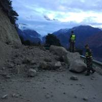 Rescuers look at a road blocked by fallen rocks near the town of Paizhen in southwestern China's Tibet Autonomous Region on Saturday after a strong earthquake shook the area. | AP