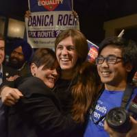 Danica Roem (center), who ran for house of delegates against GOP incumbent Robert Marshall, is greeted by supporters as she prepares to give her victory speech with the Prince William County Democratic Committee at Water's End Brewery on Tuesday in Manassas, Virginia. Roem will be the first openly transgender person elected and seated in a state legislature in the United States. | JAHI CHIKWENDIU / THE WASHINGTON POST / VIA AP