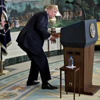 U.S. President Donald Trump looks for a water bottle while delivering remarks on his recent 11-day Asia trip in the Diplomatic Room of the White House in Washington on Wednesday. | BLOOMBERG