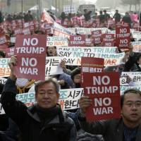 Protesters stage a rally to oppose the visit by U.S. President Donald Trump in front of South Korea's National Assembly in Seoul on Wednesday.   AP