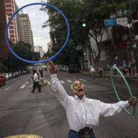 Jose Bestilleiro, 83, from Spain, performs for tips in Caracas on Sunday. Bestilleiro, who has performed for 15 years, brings in at least 5,000 Bolivars a day, which on the black market is 11 cents — the price of a cheap tortilla-like 'arepa' sandwich. | AP