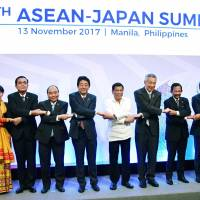 Prime Minister Shinzo Abe and his counterparts from the Association of Southeast Asian Nations take part in a photo session ahead of their annual summit Monday in Manila. | KYODO