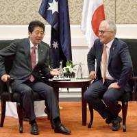 Prime Minister Shinzo Abe talks with Australian Prime Minister Malcolm Turnbull in Manila on Monday. | KYODO