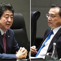 Prime Minister Shinzo Abe and Chinese Premier Li Keqiang talk in Manila on Monday. | KYODO