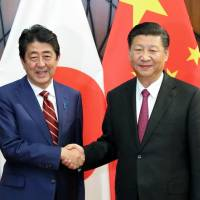 Prime Minister Shinzo Abe (left) and Chinese President Xi Jinping pose ahead of their summit meeting Saturday on the sidelines of a regional economic summit in Danang, Vietnam. | KYODO