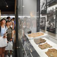 Elementary school students look at items related to the 1945 U.S. atomic bombing of Nagasaki at the Atomic Bomb Museum in the city of Nagasaki in August. Personal belongings left by hibakusha of Hiroshima and Nagasaki are expected to be exhibited in Oslo. | KYODO