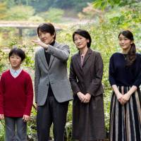 Prince Akishino gestures while strolling with his wife, Princess Kiko, in the garden with their children, Prince Hisahito and Princess Mako, at their residence in the Akasaka Imperial Grounds in Tokyo on Nov. 4. | REUTERS