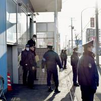 Police officers stand guard during a search of a facility believed to be used by the Aum Shinrikyo successor group Aleph in Sapporo on Monday. | KYODO