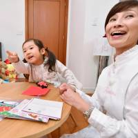 A girl plays with her baby sitter at a home in Tokyo's Minato Ward. Working mothers are increasingly depending on baby sitters to deal with a shortage of day care services. | KYODO