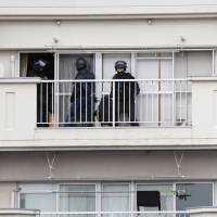 Police officers stand outside a seventh-floor apartment in Kitakyushu on Wednesday where a man with a hunting rifle barricaded himself in and later committed suicide. | KYODO