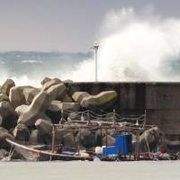 A fishing boat that washed ashore with eight North Korean men is seen Friday in Yurihonjo, Akita Prefecture. On Saturday, it disappeared from the port where it was moored, police said. | KYODO