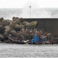 A fishing boat that washed ashore with eight North Korean men aboard is seen Friday in Yurihonjo, Akita Prefecture. The boat, which disappeared on Saturday, has been found on the seabed.   KYODO