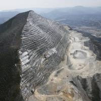 An aerial photo of Mount Buko taken in 2013 shows its northern slope scarred by decades of limestone mining. | KYODO