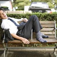 A man takes a snooze on a bench in central Tokyo, Japan..Photographer: Rob Gilhooly
