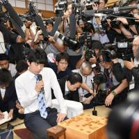 Pro shogi player Sota Fujii speaks to the media after getting his record-setting 29th straight victory at Shogi Kaikan hall in Tokyo in June. | KYODO