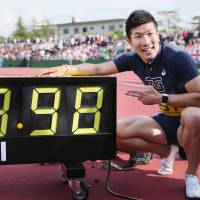 Yoshihide Kiryu poses in front of his official time after winning the 100 meters at an intercollegiate meet in Fukui. | KYODO