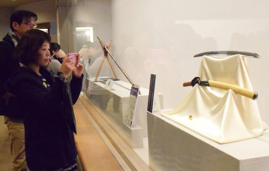 A woman takes a picture of the legendary sword Heshikiri Hasebe diplayed at Fukuoka City Museum.