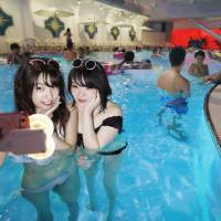Two women take selfies at a night pool at the Hotel New Otani in July. | KYODO