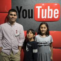 Greg Lam poses for a picture with his two children, Shintaro and Aiko, at YouTube's main offices in Tokyo.