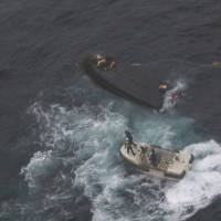A Japan Coast Guard vessel approaches a capsized North Korean fishing boat in the Sea of Japan on Wednesday. | JAPAN COAST GUARD