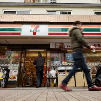 A pedestrian walks past a 7-Eleven in Kawasaki in April 2016. Convenience stores have thrived in Japan, supplanting the country's mom-and-pop stores. | BLOOMBERG